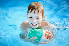 El muchacho con la bola en la piscina Imagenes de archivo