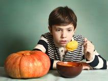 El muchacho con la calabaza anaranjada grande come la sopa poner crema del puré Imagen de archivo libre de regalías