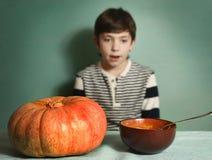 El muchacho con la calabaza anaranjada grande come la sopa poner crema del puré Imagen de archivo
