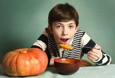 El muchacho con la calabaza anaranjada grande come la sopa poner crema del puré Fotos de archivo