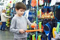 El muchacho con la estafa y la bola para el tenis de la playa en deporte hacen compras Foto de archivo