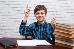 El muchacho con la mano aumentada tiene una idea Colegial que señala arriba el suyo adentro Imagen de archivo