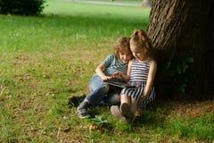 El muchacho con la muchacha de 7-8 años se sienta debajo de un árbol viejo y mira emocionado la pantalla del ordenador portátil Imagen de archivo