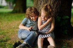 El muchacho con la muchacha de 7-8 años se sienta debajo de un árbol viejo y mira emocionado la pantalla del ordenador portátil Fotografía de archivo