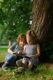 El muchacho con la muchacha de 7-8 años se sienta en la tierra debajo de un árbol y el juego en la tableta Fotografía de archivo
