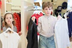 El muchacho con la muchacha que intenta en la ropa Imagenes de archivo