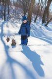 El muchacho con la rama se coloca en la nieve Imagenes de archivo