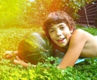 El muchacho con la sandía entera pone en la hierba verde Imagen de archivo libre de regalías