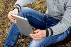 El muchacho con la tableta en sus manos se sienta en la hierba Lectura en Foto de archivo libre de regalías