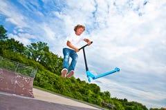 El muchacho con la vespa va aerotransportado Imagen de archivo libre de regalías