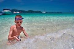 El muchacho con las gafas de la natación se sienta en el agua de la turquesa de la línea tropical de la resaca del mar Imagen de archivo libre de regalías