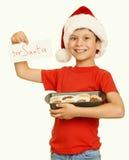 El muchacho con las galletas para santa, concepto de la Navidad de las vacaciones de invierno, amarillea entonado Fotografía de archivo