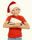 El muchacho con las galletas para santa, concepto de la Navidad de las vacaciones de invierno, amarillea entonado Foto de archivo libre de regalías