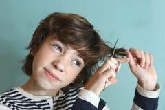 El muchacho con las tijeras intenta cortar su pelo fotos de archivo