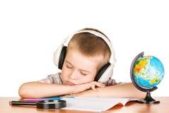 El muchacho con los auriculares, el caer dormido en el cuaderno, aisló el owhite Fotografía de archivo