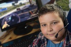 El muchacho con los auriculares está jugando a un juego de ordenador Foto de archivo libre de regalías