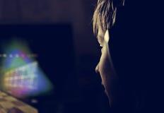 El muchacho con los auriculares mira el monitor Imagen de archivo libre de regalías