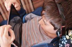 El muchacho con los auriculares mira en la tableta Foto de archivo