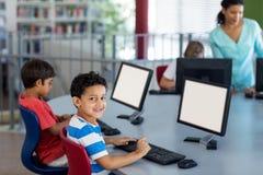El muchacho con los compañeros de clase y el profesor durante el ordenador clasifican Imágenes de archivo libres de regalías