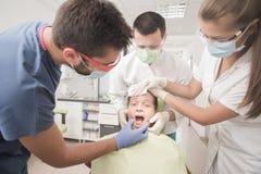El muchacho con los dientes perfectos asustó en el dentista Imágenes de archivo libres de regalías