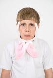 El muchacho con los oídos de conejo hace caras Fotografía de archivo