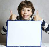 El muchacho con los pulgares detiene la hoja del papel en blanco Fotos de archivo libres de regalías