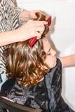 El muchacho con el pelo largo consigue su pelo para cortar por el peluquero Foto de archivo
