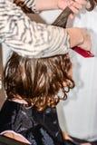 El muchacho con el pelo largo consigue su pelo para cortar por el peluquero Imágenes de archivo libres de regalías
