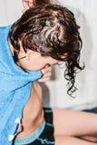 El muchacho con el pelo largo consigue su pelo para cortar por el peluquero Foto de archivo libre de regalías