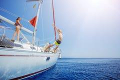 El muchacho con su hermana salta del yate de la navegación en travesía del verano Aventura del viaje, navegando con el niño Fotos de archivo