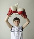 El muchacho con sus manos aumentó en guantes de boxeo en un gesto de la victoria con una estatuilla de un boxeador Fotos de archivo libres de regalías