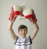 El muchacho con sus manos aumentó en guantes de boxeo en un gesto de la victoria con una estatuilla de un boxeador Imagen de archivo