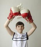 El muchacho con sus manos aumentó en guantes de boxeo en un gesto de la victoria con una estatuilla de un boxeador Fotografía de archivo libre de regalías