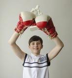 El muchacho con sus manos aumentó en guantes de boxeo en un gesto de la victoria con una estatuilla de un boxeador Imagen de archivo libre de regalías