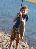 El muchacho con un grayling de giro del retén fotografía de archivo