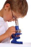 El muchacho con un microscopio Imagenes de archivo