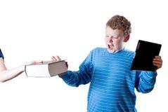 El muchacho con un ordenador de la tablilla empuja el libro Imagenes de archivo