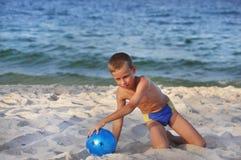 El muchacho con una bola en una playa Fotografía de archivo libre de regalías