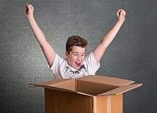 El muchacho con una caja de cartón grande es feliz Foto de archivo libre de regalías