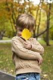 El muchacho con una hoja amarilla de un árbol Fotografía de archivo
