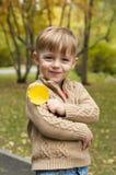 El muchacho con una hoja amarilla de un árbol Imagen de archivo libre de regalías