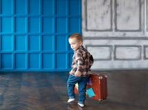 El muchacho con una maleta en el cuarto grande Foto de archivo
