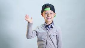 El muchacho con una sonrisa desdentada que agita su mano almacen de metraje de vídeo