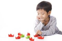 El muchacho concentrado juega las naves de papel en la tabla Foto de archivo