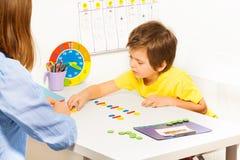 El muchacho concentrado pone monedas coloridas durante el ABA Foto de archivo