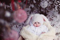 El muchacho-conejo debajo del árbol de navidad Foto de archivo