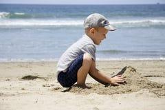 El muchacho construye un castillo de la arena en la orilla Foto de archivo