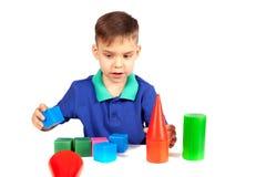 El muchacho construye una casa de cubos foto de archivo