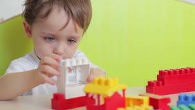El muchacho construye una casa fuera de bloques coloreados de Lego en la tabla almacen de metraje de vídeo