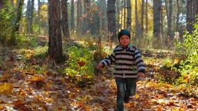 El muchacho corre con la cámara lenta del bosque del otoño almacen de metraje de vídeo